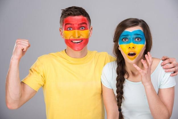 Twee fans met de vlaggen van hun land geschilderd op gezichten. Premium Foto