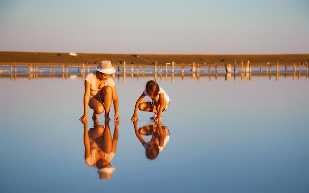 Twee fantastisch mooie meisjes in ongewone outfits op een prachtig transparant zoutmeer zoeken iets in een glanzend oppervlak Premium Foto