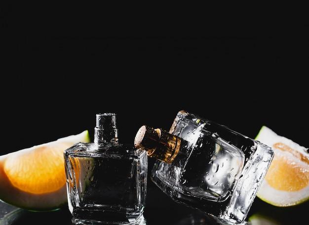 Twee flessen parfums met citrus over zwart Premium Foto