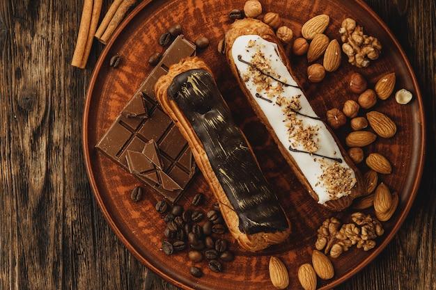 Twee geglazuurde eclairs versierd met noten en koffiebonen Premium Foto