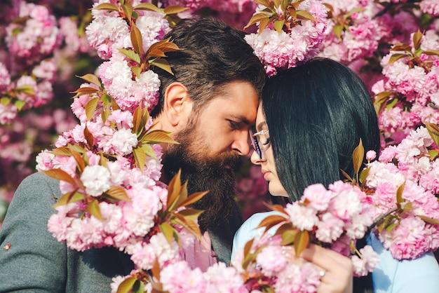 Twee geliefden knuffelen en zoenen buitenshuis. fijne valentijnsdag. jong romantisch paar onder roze sakurabloemen. liefde. lentedag. Premium Foto