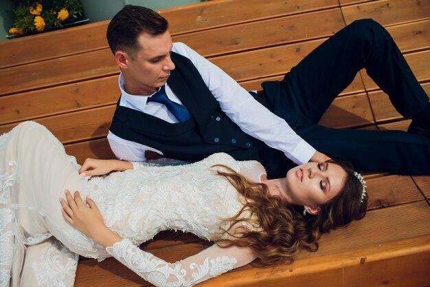 Twee geliefden zitten op een bank, jonggehuwden gehurkt om in elkaars armen te rusten tijdens een trouwfotoshoot, de bruid in een witte jurk en de bruidegom in een prachtig pak gepensioneerd in het park. Premium Foto