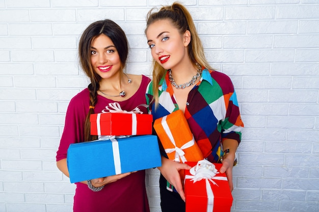 Twee gelukkige beste vrienden met heldere geschenken en cadeautjes Gratis Foto