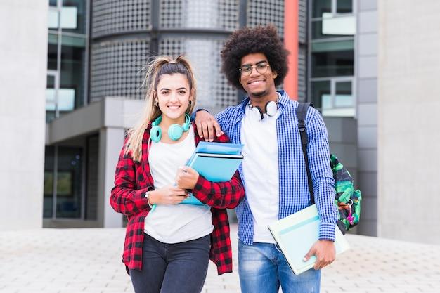 Twee gelukkige jonge studenten die aan camera kijken die zich voor de universitaire bouw bevinden Gratis Foto