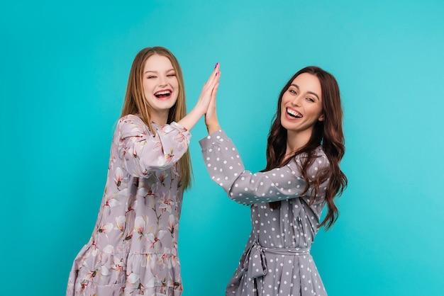 Twee gelukkige jonge vrouwen die geïsoleerde hoogte vijf geven aan elkaar Premium Foto