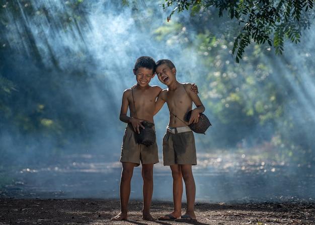 Twee gelukkige jongens en glimlachen bij openlucht, platteland van thailand Premium Foto