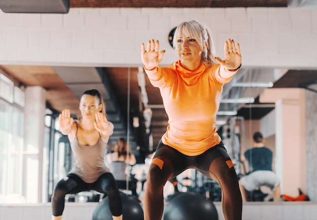 Twee gelukkige kaukasische vrouwen in sportkleding die uithoudingsvermogen in gehurkte positie in gymnastiek doen. in achtergrondspiegel. Premium Foto