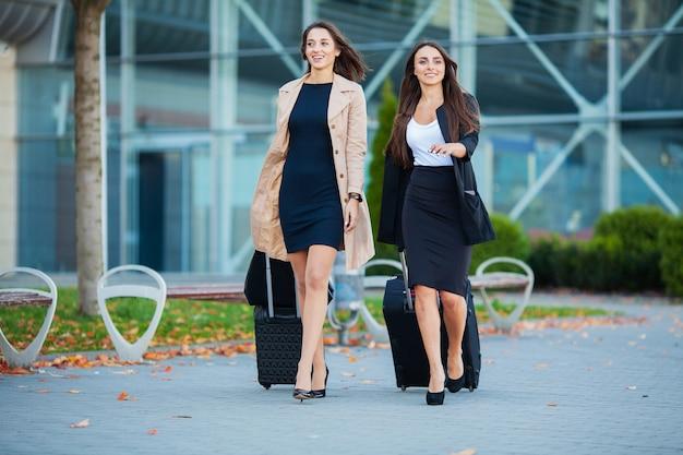 Twee gelukkige meisjes die samen naar het buitenland reizen, die kofferbagage in luchthaven dragen Premium Foto