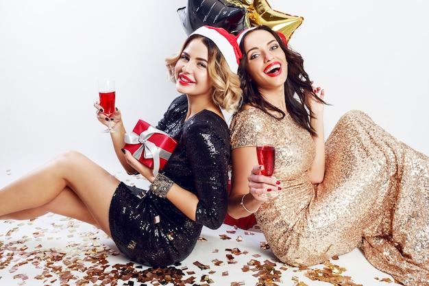 Twee gelukkige meisjes in in rode kerst kerstman vakantie hoed zittend op de vloer, wijn drinken, lachen, samen genieten van tijd Gratis Foto