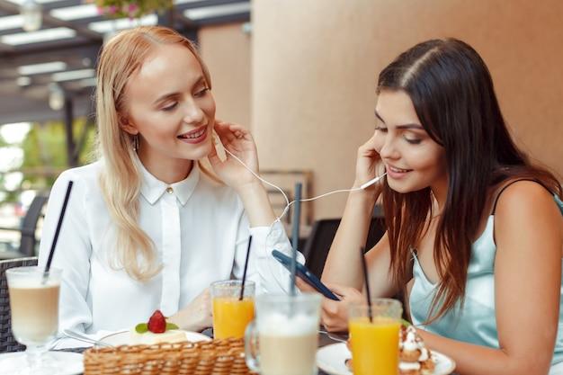 Twee gelukkige meisjes luisteren naar muziek met gedeelde oortelefoons samen in een leuk café. geniet van muziek en entertainment Premium Foto