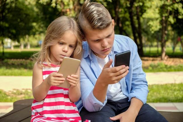 Twee gelukkige tienervrienden die op mobiele telefoon gebruiken terwijl het ontspannen in het park Premium Foto