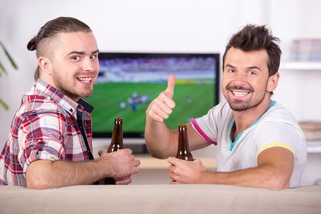 Twee gelukkige voetbalfans tijdens het kijken naar favoriete team op tv. Premium Foto