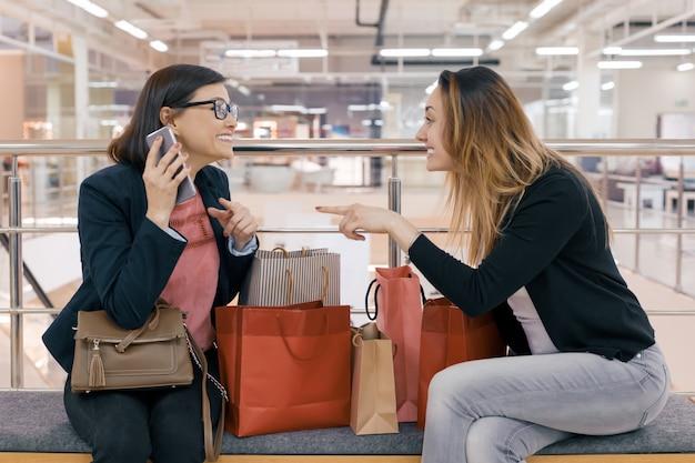 Twee gelukkige volwassen vrouwenvrienden met het winkelen zakken Premium Foto