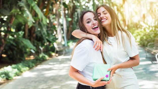Twee gelukkige vrienden met geschenkdoos knuffelen elkaar Gratis Foto