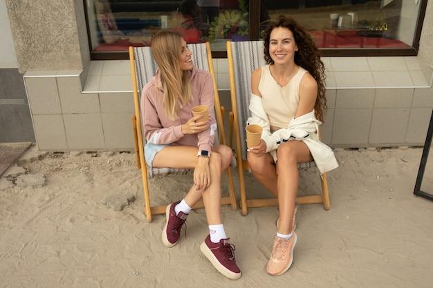 Twee gelukkige vrienden praten tijdens een gesprek in een coffeeshop Premium Foto