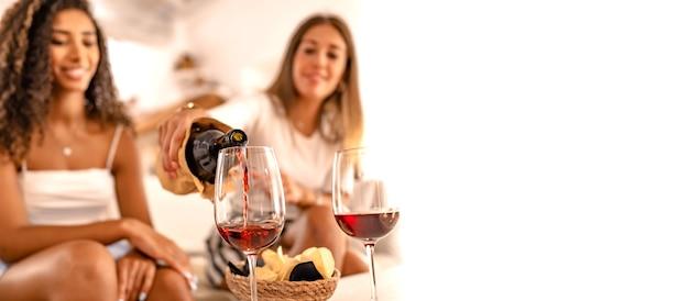 Twee gelukkige vriendinnen vieren thuis rode wijn gieten in de glazen in selectieve focus effect en kopie ruimte. jonge blanke vrouw roosteren met haar beste spaanse vriend alcohol drinken Premium Foto