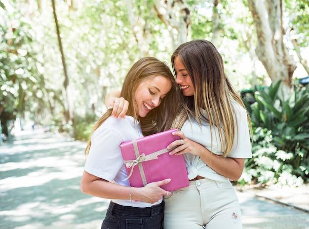 Twee gelukkige vrouwelijke vrienden met roze geschenkdoos Gratis Foto