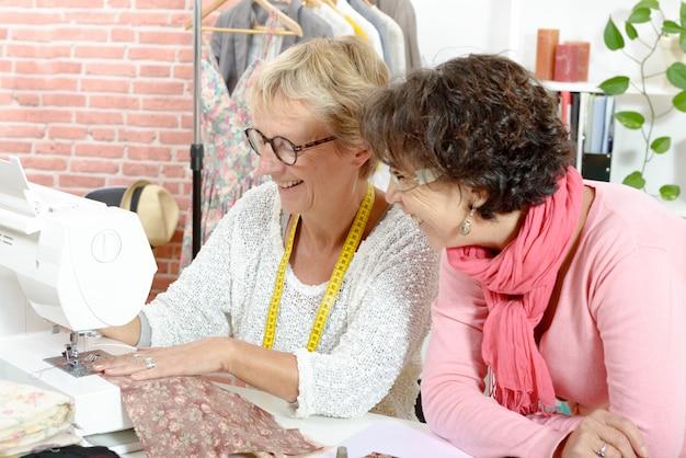 Twee gelukkige vrouwen die in hun workshop naaien Premium Foto