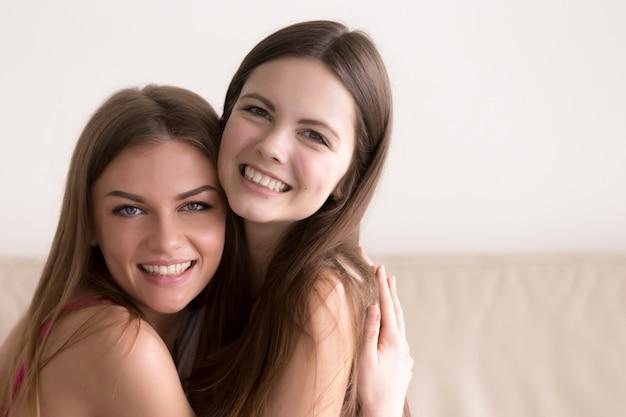 Twee gelukkige vrouwen knuffelen en kijken in de camera Gratis Foto