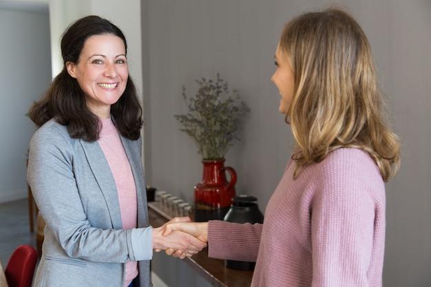 Twee gelukkige vrouwen staan en handen schudden Gratis Foto