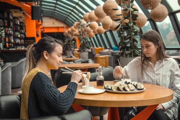 Twee gelukkige vrouwen zitten in een cafe, sushi eten Gratis Foto