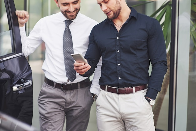 Twee gelukkige, zelfverzekerde jonge zakenlieden staan bij het kantoor. Gratis Foto