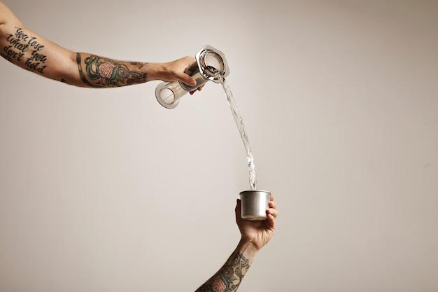 Twee getatoeëerde man's handen gieten water uit een doorzichtige plastic aeropress in een kleine stalen reisbeker op wit alternatieve koffie brouwen commerciële Gratis Foto
