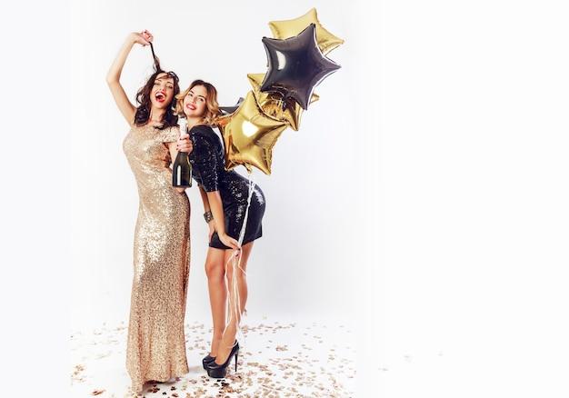 Twee geweldige sexy vieren vrouw met rode lippen, lachen, poseren. een fles champagne vasthouden, plezier maken. volledige lengte. Gratis Foto