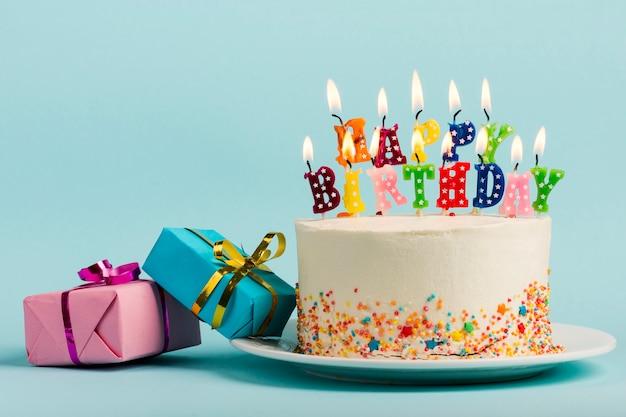Twee giftdozen dichtbij de cake met gelukkige verjaardagskaarsen tegen blauwe achtergrond Gratis Foto