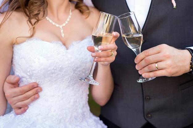 Twee glazen champagne in de handen van de bruid en bruidegom Premium Foto