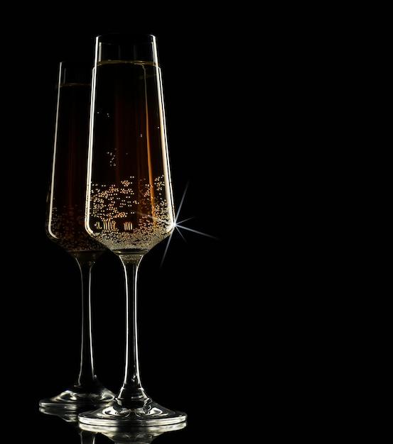Twee glazen champagne op een zwarte achtergrond Premium Foto