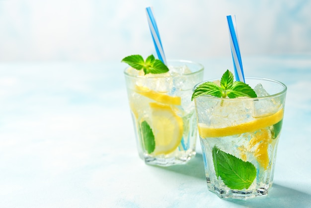 Twee glazen limonade met verse citroen op turkooise achtergrond, met exemplaarruimte Premium Foto