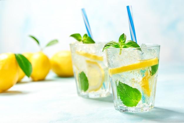 Twee glazen limonade met verse citroen op turkooise achtergrond Premium Foto