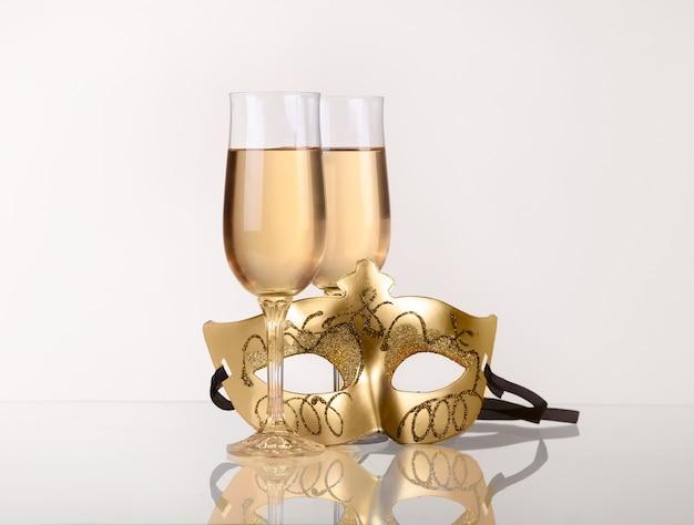 Twee glazen met champagne op een tafel met maskerade masker Premium Foto