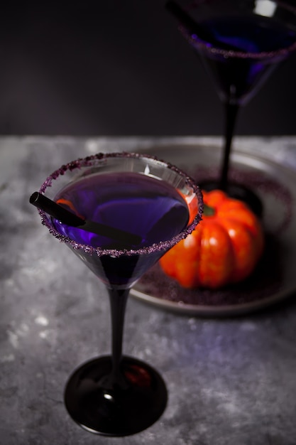 Twee glazen met paarse cocktail, pompoen voor donkere halloween-partij Premium Foto