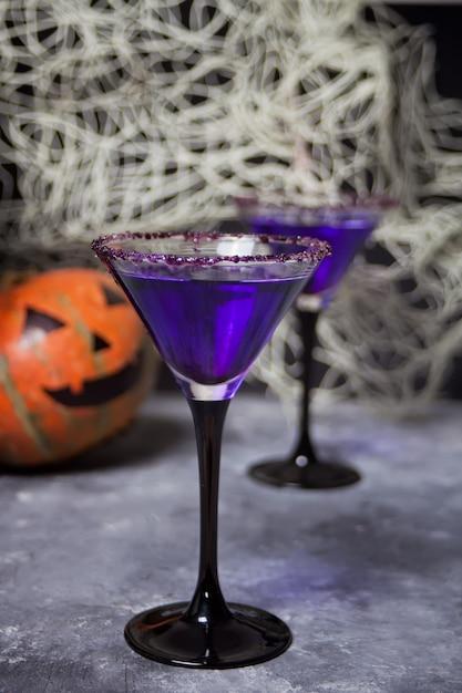 Twee glazen met paarse cocktail, pompoen voor halloween-feest Premium Foto