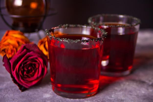 Twee glazen met rode cocktail, gedroogde rozen voor halloween-feest in het donker Premium Foto
