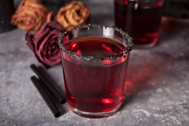 Twee glazen met rode cocktail, gedroogde rozen voor halloween-feest op de donkere achtergrond Premium Foto