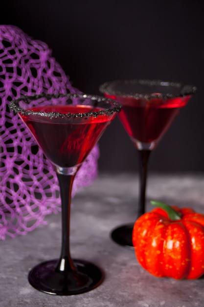 Twee glazen met rode cocktail voor halloween-feest op dark Premium Foto