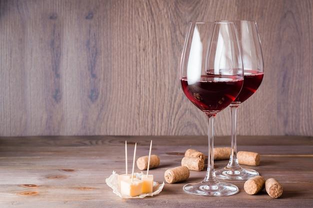 Twee glazen met rode wijn, stukjes kaas en kurk op een houten tafel Premium Foto