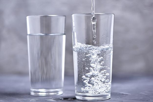Twee glazen met water op een onscherpe achtergrond. giet water in een glas. Premium Foto