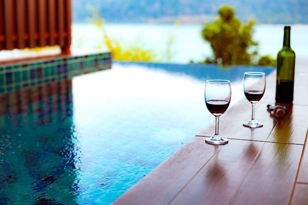 Twee glazen rode wijn bij het zwembad met een spectaculair uitzicht op de zee Premium Foto