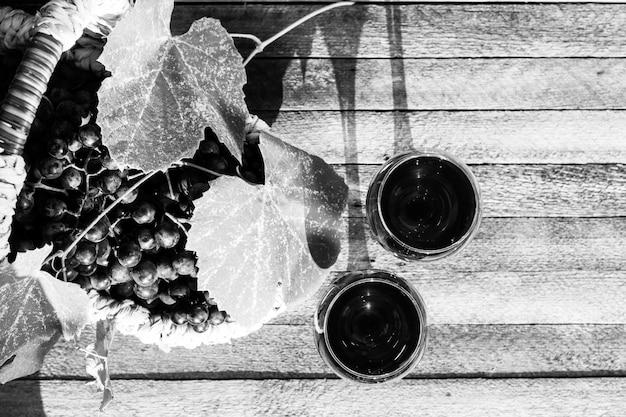 Twee glazen rode wijn en een mand met druiven op een houten achtergrond Premium Foto