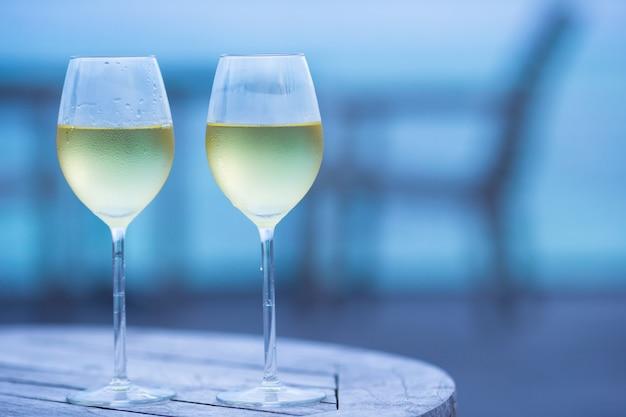 Twee glazen smakelijke witte wijn bij zonsondergang Premium Foto