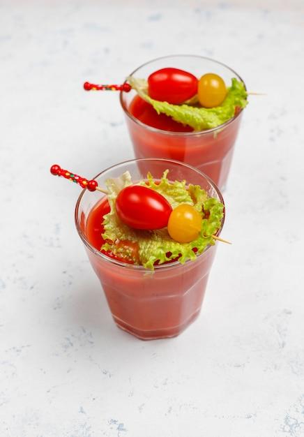 Twee glazen vers tomatesap en tomaten op grijze concrete oppervlakte Gratis Foto