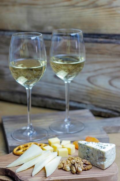 Twee glazen witte wijn met kaasplank op rustieke met verschillende kaas, blauwe kaas, gauda en noten en snacks Gratis Foto