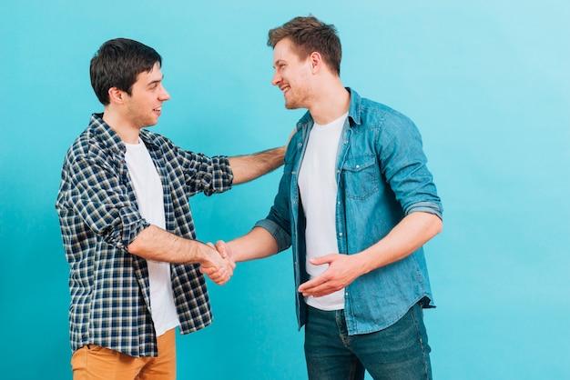 Twee glimlachende jonge mensen die handen schudden tegen blauwe achtergrond Gratis Foto