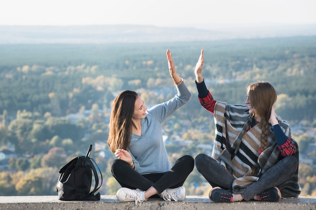 Twee glimlachende meisjes die pretzitting op een heuvel hebben. zonnige dag Premium Foto