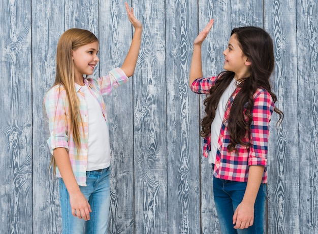 Twee glimlachende meisjes die zich tegen grijze houten muur bevinden die hoogte vijf geven Gratis Foto
