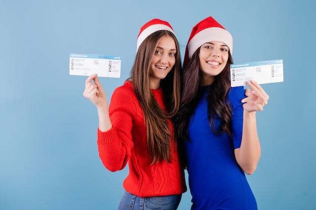Twee glimlachende vrouwen die santahoeden met vliegtuigkaartjes dragen die over blauw worden geïsoleerd Premium Foto